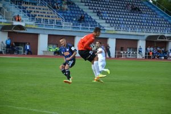 Dubnický brankár M. Slávik zasahuje pred hráčom Slovana B Mikušom (v modrom).