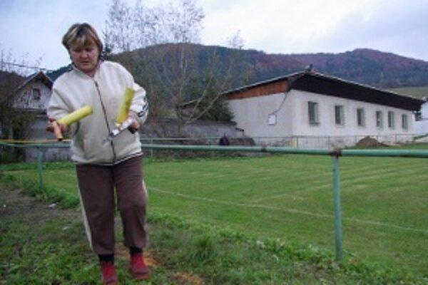 Daniela Bobuľová zbiera dymovnice. Za chrbtom je jej chatka, vedľa sporná budova na ihrisku.
