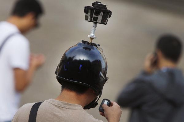 Čínsky turista s kamerou na diaľkové ovládanie na helme.