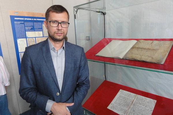 Peter Keresteš pri dvoch najvzácnejších dokumentoch - konfirmácii z 5. mája 1632 (hore) a najstaršej mestskej zápisnici z rokov 1681-93.