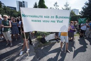Účastníci s transparentmi počas protestného zhromaždenia v areáli SAV na Patrónke, vyzývajú ministerstvo školstva, aby zapísalo nové verejné výskumné inštitúcie do registra.