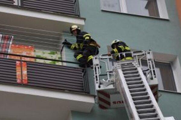 Hasiči vchádzajú na balkón na piatom poschodí.