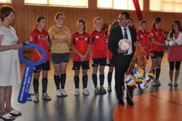 Riaditeľka školy so starostom a futbalistkami v novej športovej hale.