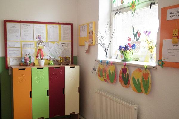 V šatni zdobia steny a okná prácami detí a učiteľov, aby nebolo vidieť nedostatky.