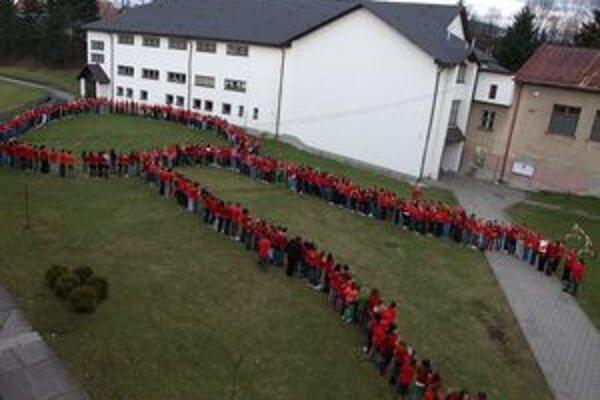 Celá škola prišla oblečená včervených tričkách, aby spoločne vytvorili obrovskú červenú stužku, symbol boja proti AIDS.