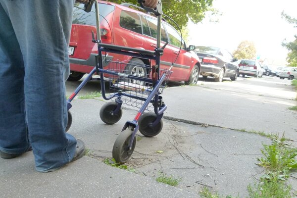 Starší pán chodí pomocou barly alebo tlačiaceho vozíka.
