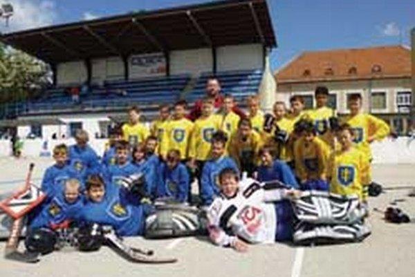 Hokejbaloví žiaci Topoľčian do 12 a 10 rokov spolu s trénerom Martinom Benkom.