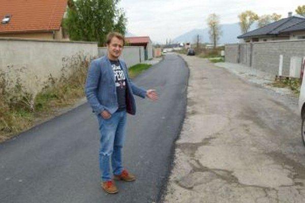 Martin Kalnický ukazuje čiastočne opravenú cestu, ktorá aspoň čiastočne zlepší autám prejazd k domom.