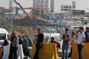 Robotníci stoja pred areálom staveniska nového letiska v Istanbule.