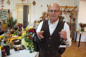 Jozef Lichtner ukazuje domáce ovocné vína, ktorých sa na prehliadke úrody objavilo viacero.
