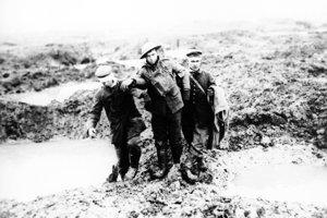 Zranený kanadský a nemecký vojak si pomáhajú prejsť cez blato v bitke o Passchendaele v Belgicku.