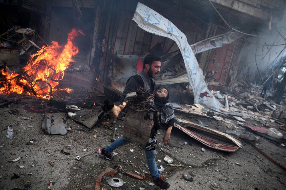 Sýrčan nesie telo mŕtveho dieťaťa zabitého pri nálete vládnych síl v sýrskej  Doume  (Druhá cena/všeobecné správy - príbehy). Abd Doumany/World Press Photo.