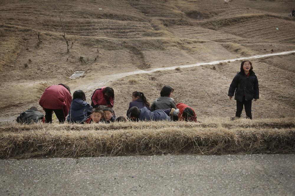 Severokórejské deti odpočívajú na okraji cesty.