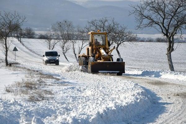 Na snímke odpratávanie snehových jazykov na ceste medzi obcami Veľká Tŕňa a Čerhov v okrese Trebišov ťažkým mechanizmom košickej Spravy ciest.
