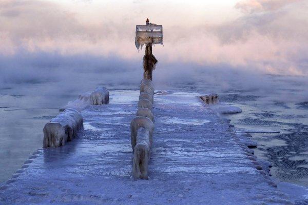 Prístavné svetlo pokryté ľadom na zamrznutom jazere Michigan v prístave v Chicagu.