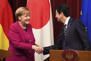 Nemecká kancelárka Angela Merkelová (vľavo) a japonský premiér Šinzo Abe (vpravo) si podávajú ruky po tlačovej konferencii v Tokiu.