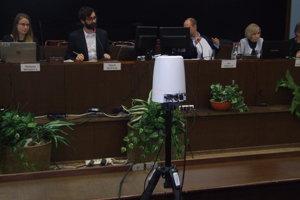 Kamera sníma primátora a ďalších ľudí za predsedníckym stolom.