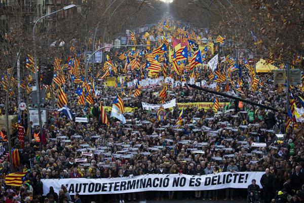 """Demonštranti mávali modro-červeno-žltými separatistickými katalánskymi zástavami a niesli transparenty so sloganom """"Slobodu pre politických väzňov""""."""