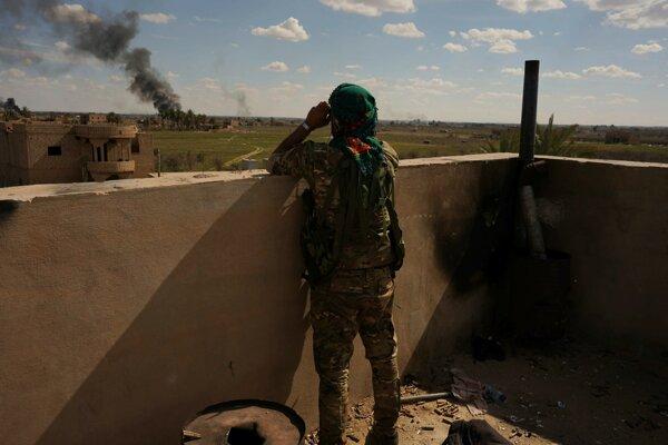 Bojovník sýrskych demokratických síl sleduje čierny dym nad poslednou baštou Islamského štátu, dedinou Baghúz.
