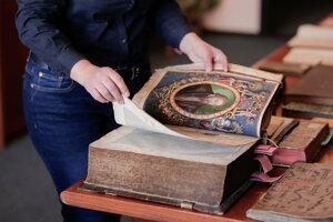 Ukážka ornamentálno - figurálnej ilustrácie knihy s kruhopisom a erbovým štítom autora s nosičmi z knihy od Pietra Andrea Mattioliho z roku 1565