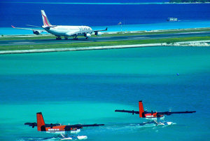 Príprava na štart. Airbus A340 na letisku v Male na Maldivoch. Súbežne s ním z hladiny lagúny štartujú dva stroje Maldivian Air Taxi.