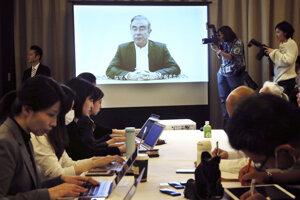 Novinári sledujú Ghosnovo video na tlačovej konferencii v Tokiu.