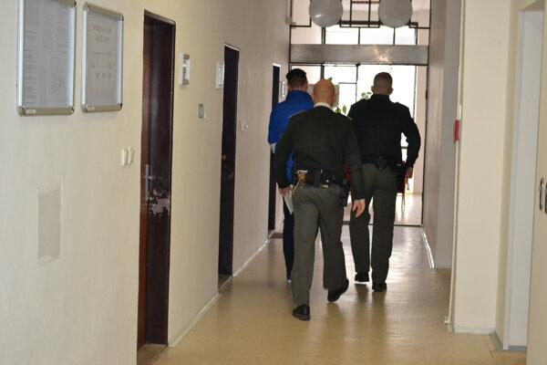 Mladého muža priviedli na súd v putách.