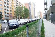 """Plot  na okraji mestského trávnika. Vpravo sú nové bytové domy, vľavo """"staré""""."""