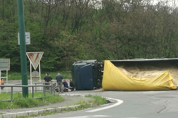 Nákladné auto skončilo v zákrute prevrátené na boku.