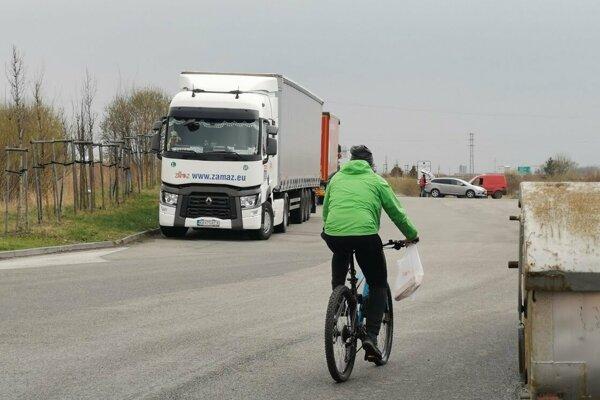 Cyklisti aj chodci chodia a jazdia po neosvetlenej ceste.