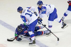 Slovenskí hokejisti bojujú o puk.