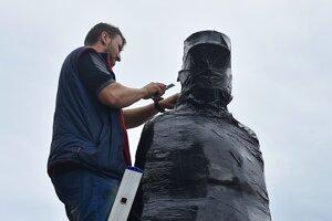 Muž odstraňuje ochrannú fóliu z hliníkovej sochy Milana Rastislava Štefánika počas pripevnenia na podstavec.