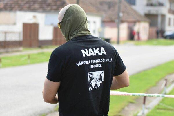 Príslušník NAKA inštaluje policajnú pásku pred začiatkom rekonštrukcie vraždy Jána Kuciaka a Martiny Kušnírovej.