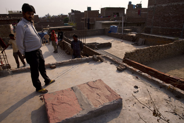Policajt stojí na streche domu, v ktorom k údajnému znásilneniu došlo.