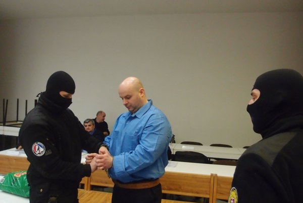 Adamča eskortovali na súd kukláči.