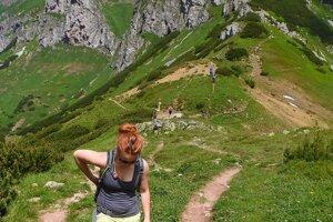 Turistka kráča po chodníku zo Širokého sedla pod Ždiarskou vidlou v Belianskych Tatrách.
