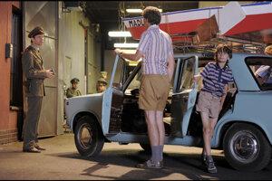 Rodina Hájekovcov z filmu Občiansky preukaz vystupuje z auta. O malú chvíľu colníci prekontrolujú celé ich auto.