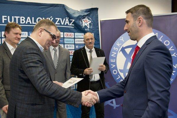 Martin Ševela (vpravo) si ako nový držiteľ najvyššej UEFA PRO licencie preberá z rúk šéfa SFZ Jána Kováčika diplom počas slávnostného oceňovania.
