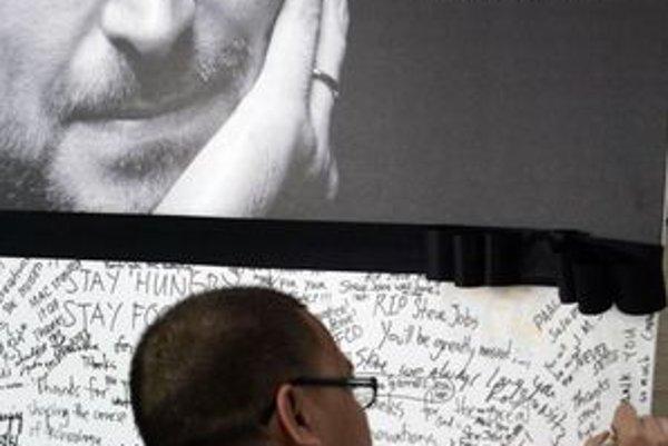 Ľudia píšu kondolenčné odkazy pred jedným z obchodov Apple.