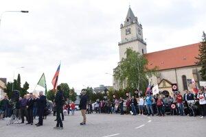 Zhromaždenie ĽSNS a za nimi protestujúci počas tichého protestu proti fašizmu, rasizmu a neznášanlivosti v Hlohovci v máji 2019.