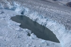 Miesto, kde na ľadovci Helheim dochádza k teleniu, teda odlamovaniu obrovských kusov ľadu. Teploty boli také vysoké, že časť ľadu sa roztopila a odhalila vodu.