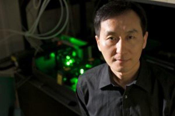 """Chunlei Guo z Rochesterskej univerzity (štát New York, USA) vo svojom laboratóriu pred """"čarodejným"""" femtosekundovým laserom. V spolupráci najmä s asistentom Anatolijom Vorobjevom ním okrem iného dokázal zdvojnásobiť účinnosť bežnej žiarovky."""
