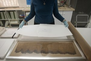 Výskumníčka Izraelského pamiatkového úradu ukazuje kópiu Zvitkov od Mŕtveho mora.