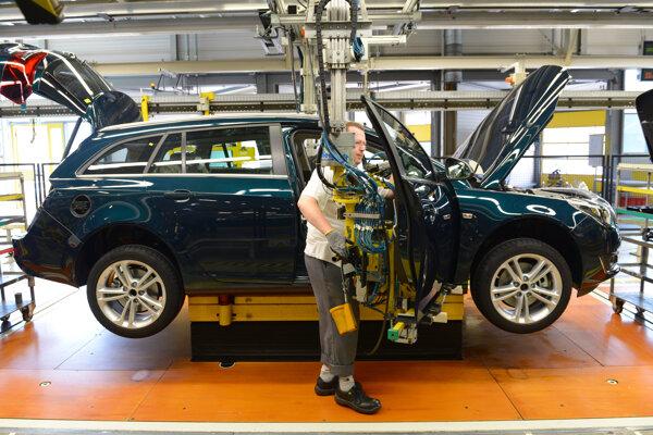 Na archívnej snímke z 22. augusta 2013 zamestnanec montuje dvere na auto v hlavnom závode automobilky Opel v nemeckom meste Rüsselsheim.