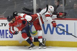 Hokejista Washingtonu Capitals Martin Fehérváry (vľavo) a hráč Caroliny Jordan Martinook bojujú pri mantineli počas zápasu zámorskej hokejovej NHL Washington Capitals - Carolina Hurricanes.