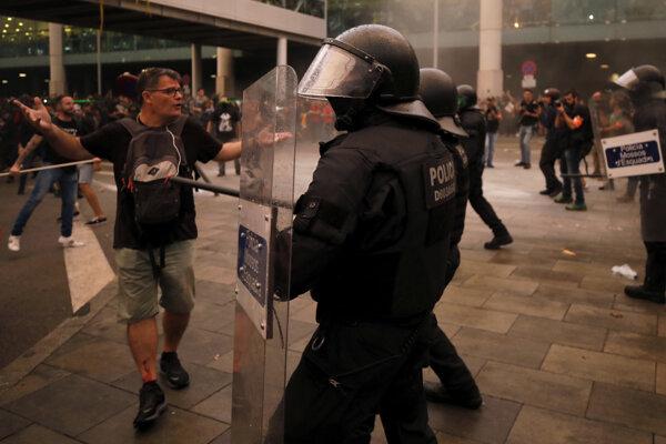 Demonštranti v kolízii s poriadkovou políciou po verdikte španielskeho najvyššieho súdu, ktorý v pondelok vymeral dlhoročné tresty väzenia deviatim bývalým katalánskym lídrom 14. októbra 2019 pred letiskom v Barcelone.