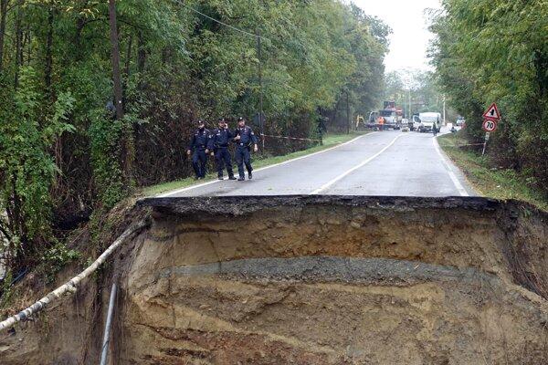 Policajti stoja pri ceste v Capriata d'Orba na severe Talianska 22. októbra 2019. Krajinu sužujú intenzívne dažde.
