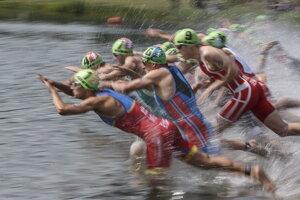 Triatlonisti skáču do vody počas plaveckej časti na šiestom podujatí Svetovej série ITU v kanadskom Edmontone 29. júla 2017.