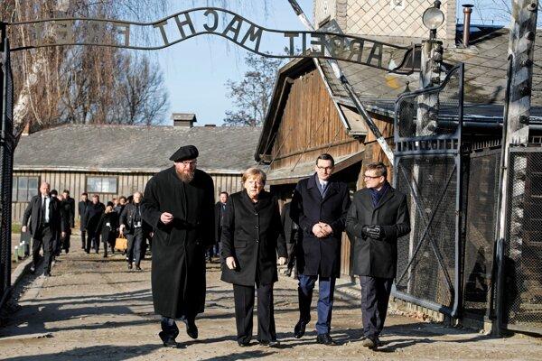 Zľava riaditeľ múzea Piotr Cywinski, nemecká kancelárka Angela Merkelová, poľský premiér Mateusz Morawiecki a zástupca riaditeľa múzea Andrzej Kacorzyk  pri vstupe do bývalého nacistického koncentračného tábora Auschwitz-Birkenau v Osvienčime 6. decembra 2019.