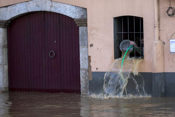 Muž vylieva vodu zo svojho domu počas potopy po búrke v španielskej Girone 23. januára 2020.